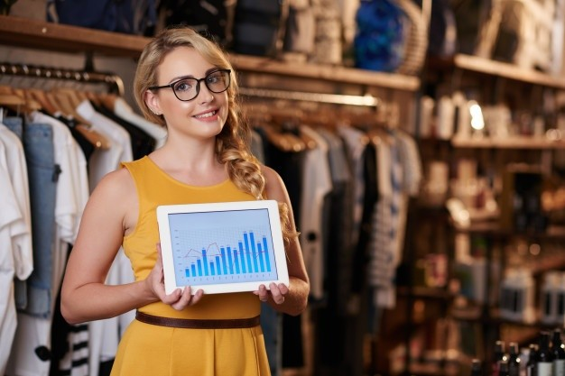 young-caucasian-woman-standing-boutique-shop-showing-tablet-with-business-graph_1098-20657.jpeg